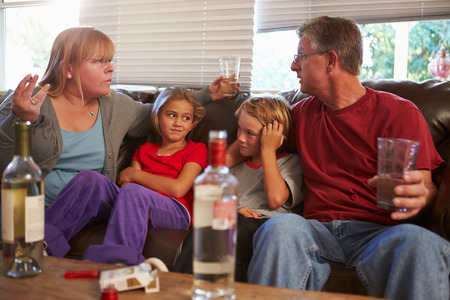 family problems: Parents Arguing On Sofa With Children Smoking And Drinking Stock Photo