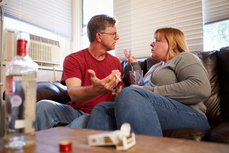 arguement: Couple Arguing On Sofa With Bottle Of Vodka And Cigarettes