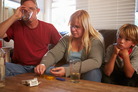 alcoholismo: Los padres se sientan en el sofá con los niños que toman drogas y beber Foto de archivo