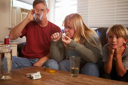drogadiccion: Los padres se sientan en el sofá con los niños que toman drogas y beber Foto de archivo