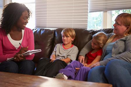 padres hablando con hijos: Trabajador social habla con la madre y los hijos en el hogar Foto de archivo
