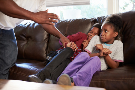 child abuse: Father Being Physically Abusive Towards Children At Home Stock Photo