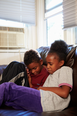 Unhappy Children Sitting On Sofa At Home photo