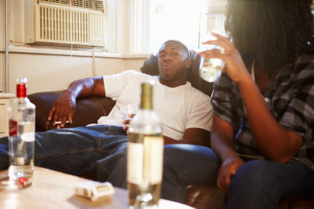 couple couch: Couple Sitting On Sofa With Bottle Of Vodka And Cigarettes Stock Photo