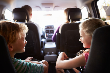 woman driving car: Children In Back Seat Of Car On Journey With Parents Stock Photo