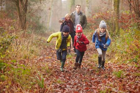persona caminando: Familia que recorre a trav�s del arbolado del invierno Foto de archivo