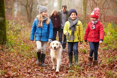familia: Familia que recorre a trav�s del arbolado del invierno del perro