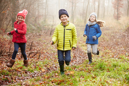 Three Children Running Through Winter Woodland