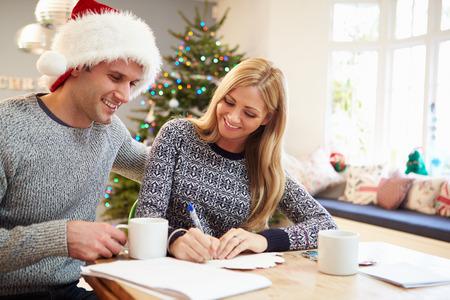 persona escribiendo: Pareja escribir tarjetas de Navidad Juntos