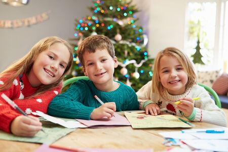 ni�os escribiendo: Tres ni�os que escribir cartas a Pap� Juntos Foto de archivo