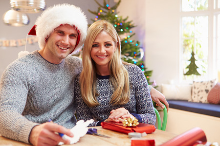 Couple Wrapping Christmas Gifts At Home photo