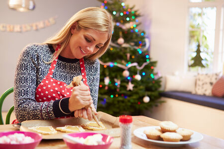 baking christmas cookies: Woman Decorating Christmas Cookies In Kitchen Stock Photo