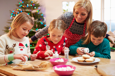 6 7 year old: Mother And Children Decorating Christmas Cookies Together Stock Photo