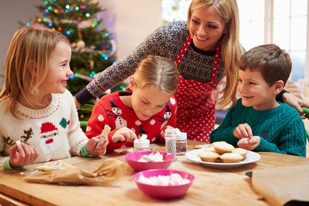 decorating christmas tree: Mother And Children Decorating Christmas Cookies Together Stock Photo