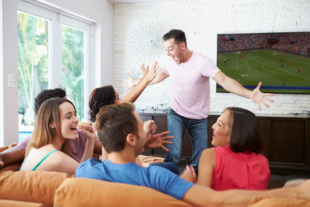 footballs: Group Of Friends Sitting On Sofa Watching Soccer Together Stock Photo
