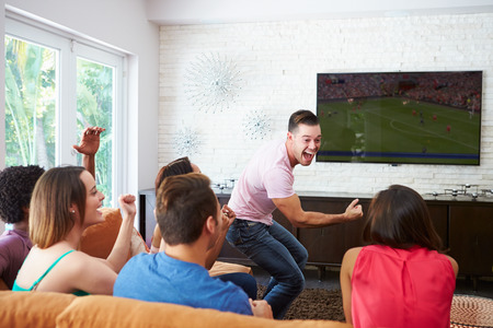 cheer: Group Of Friends Sitting On Sofa Watching Soccer Together Stock Photo