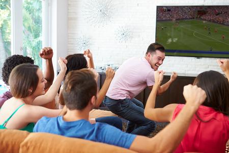 Groep vrienden kijken naar voetbal vieren doel
