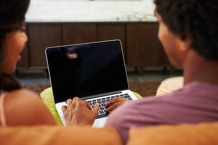 watching movie: Rear View Of Couple Sitting On Sofa Using Laptop