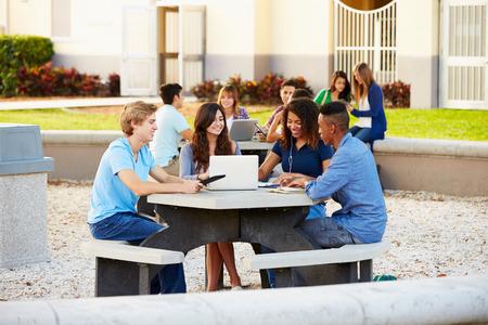 estudiantes de secundaria: Estudiantes de secundaria que cuelgan hacia fuera en el campus