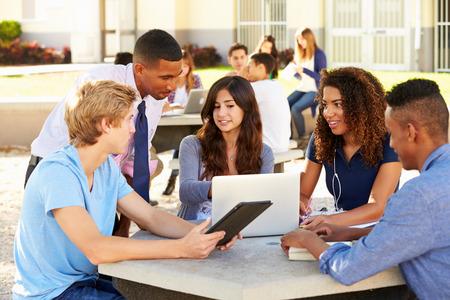 High School Students Working On Campus With Teacher Banco de Imagens