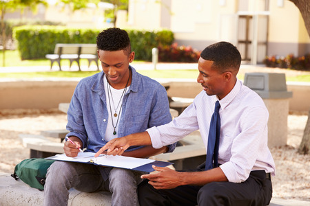 assisting: Teacher Sitting Outdoors Helping Male Student With Work Stock Photo