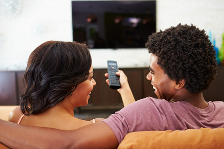 Rear View Of Couple Sitting On Sofa Watching TV Together Stock Photo