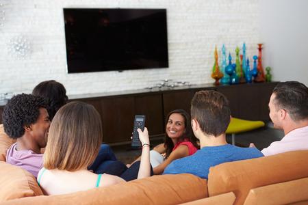 Gruppe Freunde, die sitzen auf dem Sofa vor dem Fernseher zusammen Standard-Bild