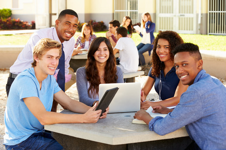 female student: High School Students Working On Campus With Teacher Stock Photo