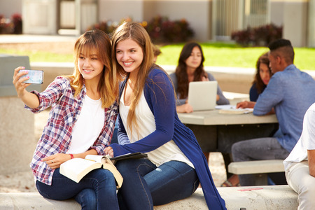 revising: Female High School Students Taking Selfie On Campus