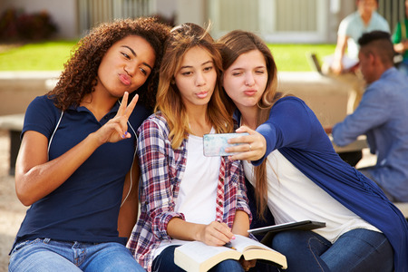 happy teenagers: Female High School Students Taking Selfie On Campus