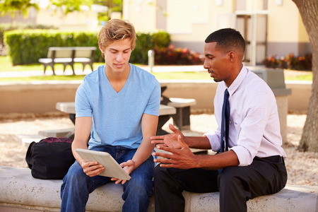 Teacher Sitting Outdoors Helping Male Student With Work photo
