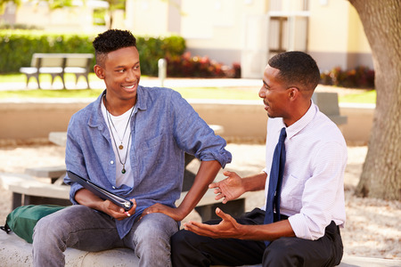 teenage male: Teacher Sitting Outdoors Helping Male Student With Work Stock Photo