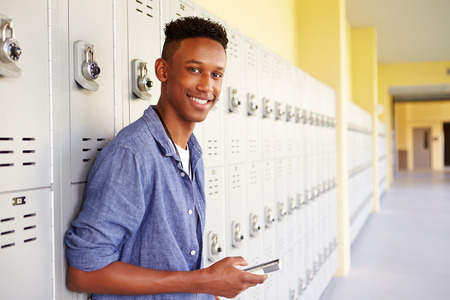 Mannelijke middelbare school student door Lockers Mobiele Telefoon met behulp