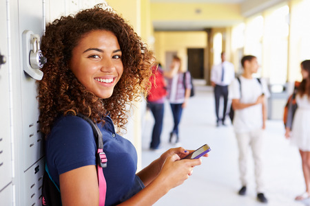 african american: Female High School Student By Lockers Using Mobile Phone Stock Photo