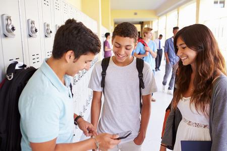 High School Studenten door Lockers Op Mobiele Telefoon Op zoek
