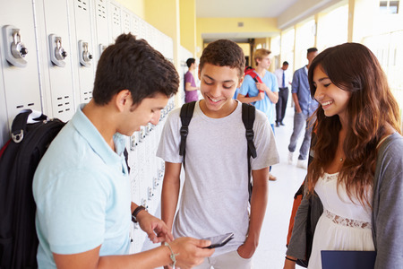 happy teenager: High School Students By Lockers Looking At Mobile Phone