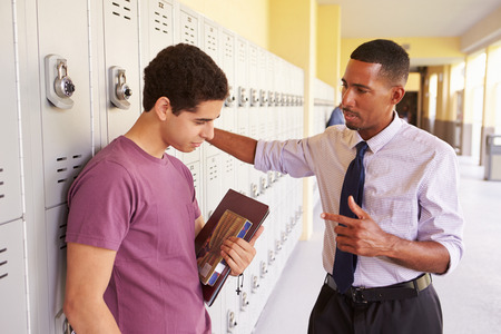 Male High School Student Talking To Teacher By Lockers photo