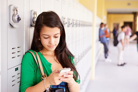 locker: Female High School Student By Lockers Using Mobile Phone Stock Photo