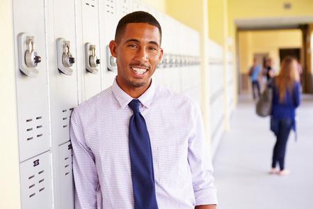 Male High School Teacher Standing By Lockers