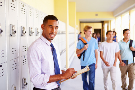 Male High School Teacher Standing By Lockers