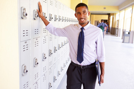 high school teacher: Male High School Teacher Standing By Lockers