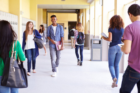 Group Of High School Students Walking Along Hallway