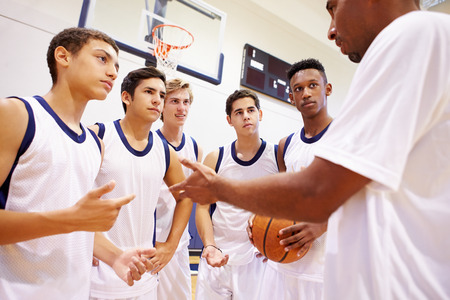 sport team: Male High School Basketball Team Having Team Talk With Coach Stock Photo