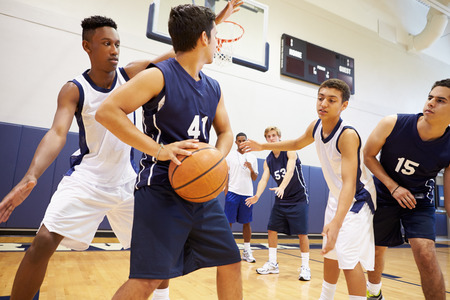 škola: Muž High School Basketball Team hraní her Reklamní fotografie