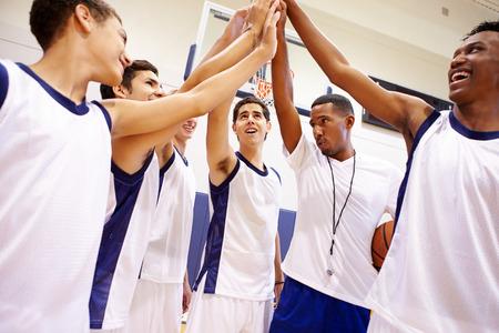 sports coach: Male High School Basketball Team Having Team Talk With Coach Stock Photo