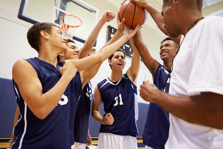 a basketball player: Male High School Basketball Team Having Team Talk With Coach Stock Photo