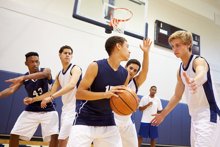 teens playing: Male High School Basketball Team Playing Game