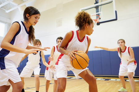 teens: Female High School Basketball Team Playing Game Stock Photo