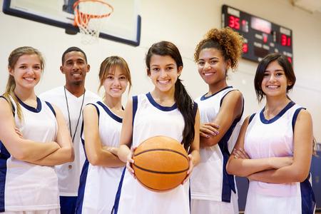 De leden van de Vrouwelijke High School Basketball Team met coach Stockfoto