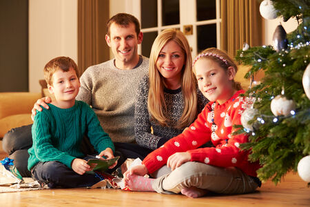 family having fun: Family Unwrapping Gifts By Christmas Tree